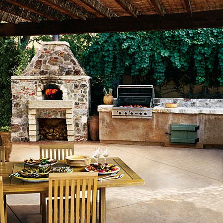outdoor kitchen with stone fireplace and shed